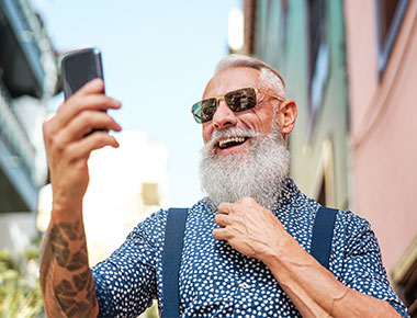 Man with grey beard, sunglasses and tattoos working via video chat walking down the street.