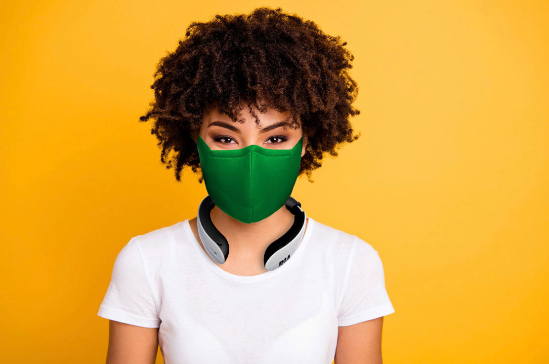 Young African American woman wearing RIA and face mask against yellow background