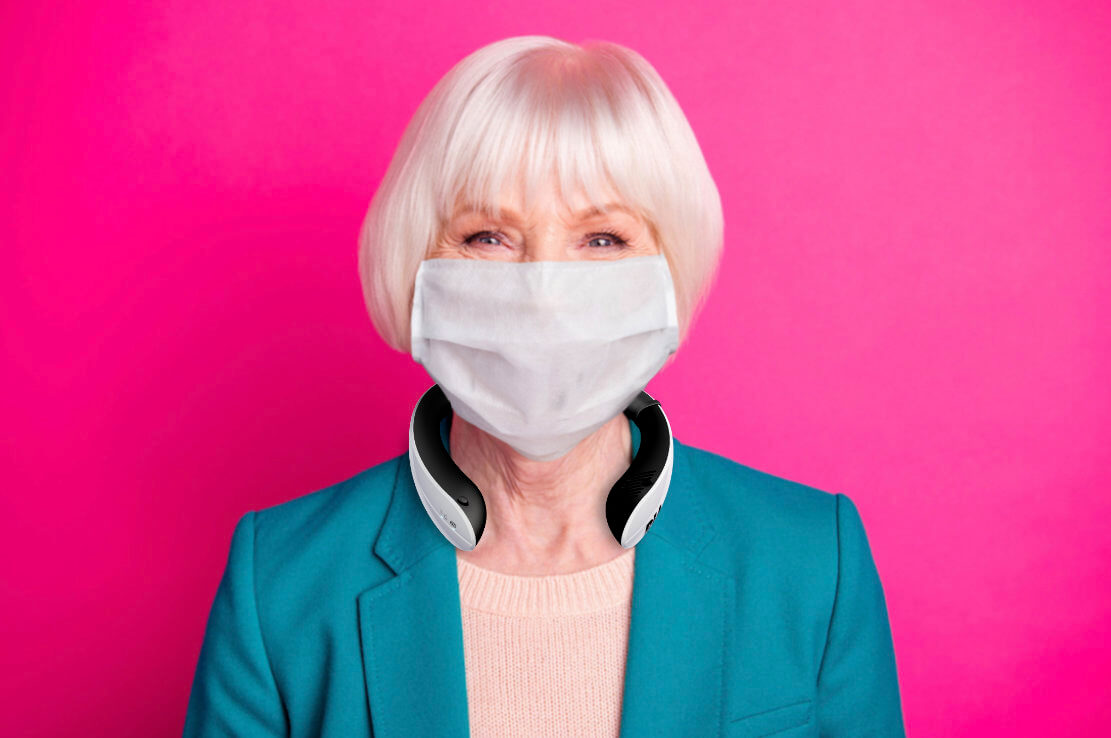 Senior woman wearing RIA and face mask against pink background