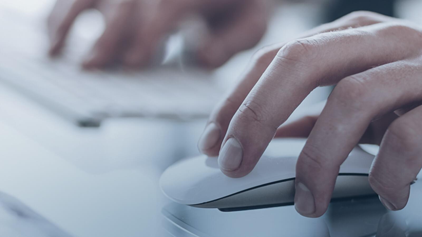 Hand arbeitet mit weißer Maus an Immobilienverwaltungssoftware