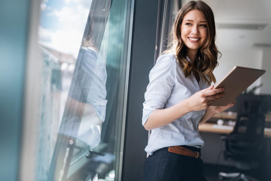 Lächelnde junge Frau mit Tablet in der Hand blickt aus dem Fenster