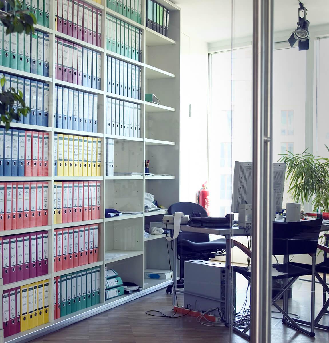Großes Regal mit Akten und Schreibtisch mir Rechner zur Datenverwaltung