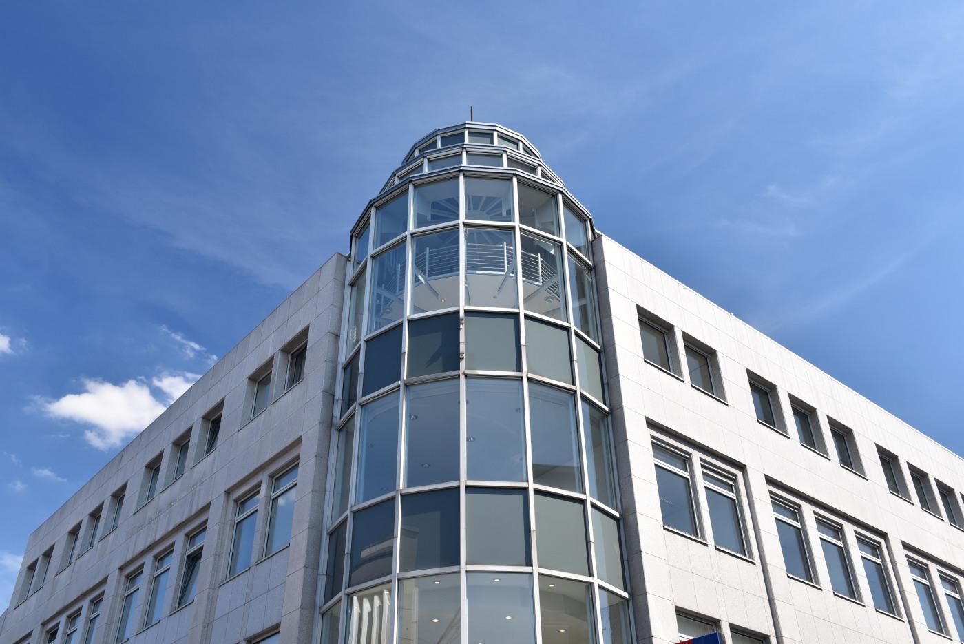 Großes Gebäude mit Glasturm bei blauem Himmel von Haufe Powerhaus