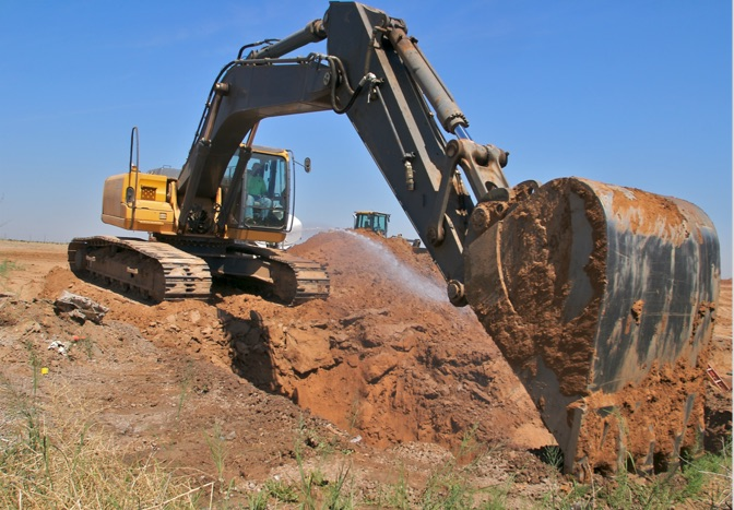excavator digging hole in field