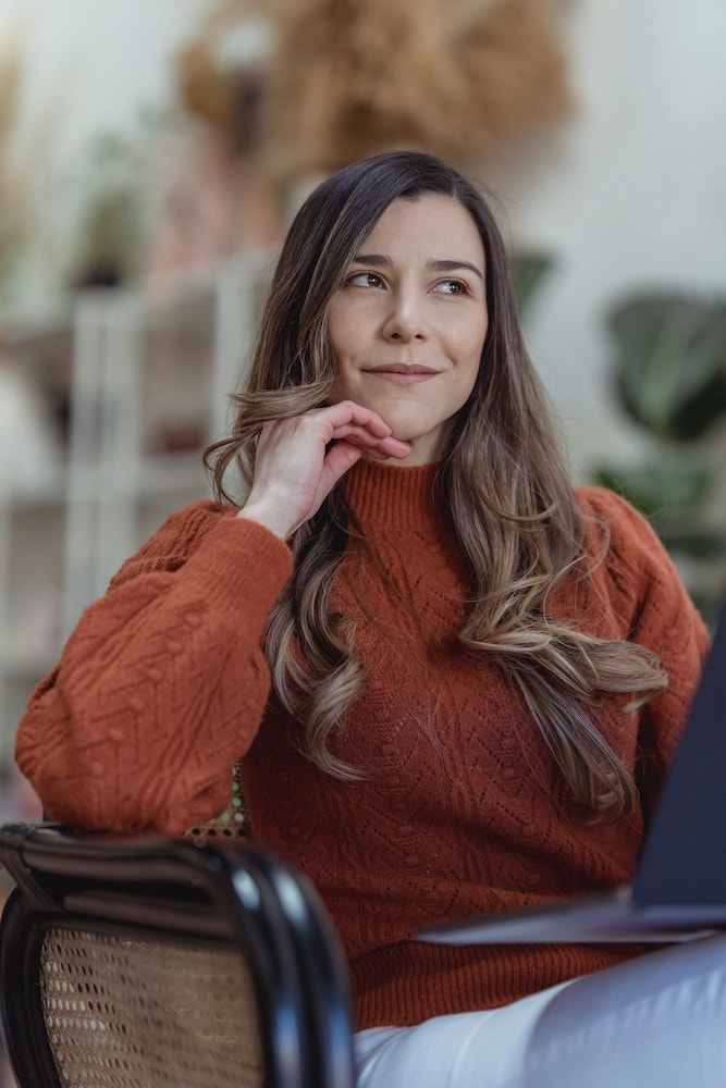 woman thinking on a bench about website design with laptop