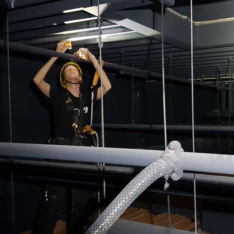 Industriekletterer bei der Überprüfung der Sprinkleranlage