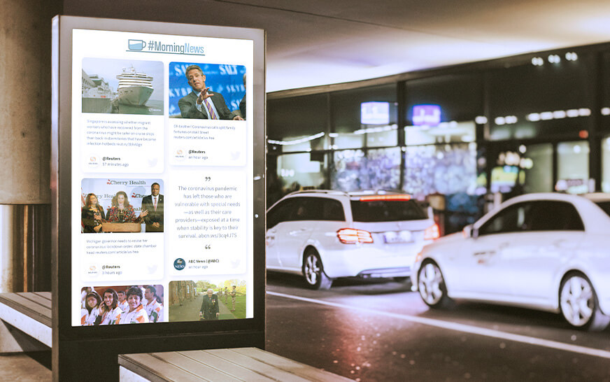 Social wall on a permanent display showing the latest morning news while a white car is passing by.
