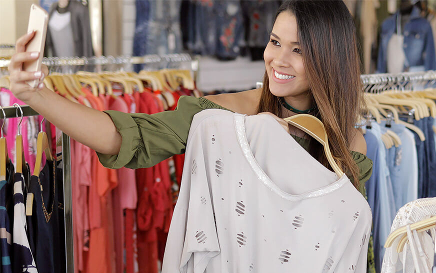 girl creating user-generated content for a fashion brand by taking a selfie inside the store