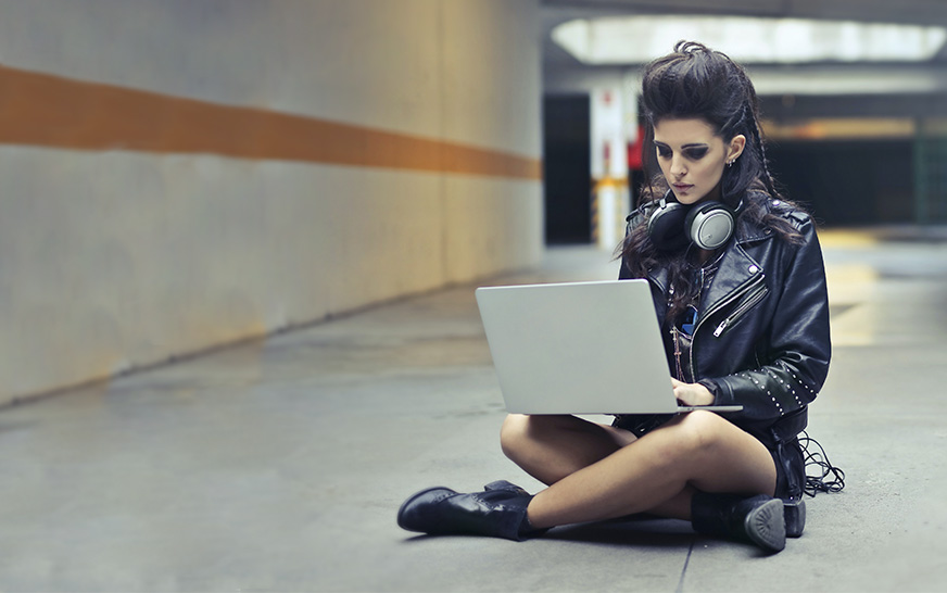Girl with headphones sitting on the floor and looking at her laptop. Featured image for the Yamaha Music London social media hub usecase.