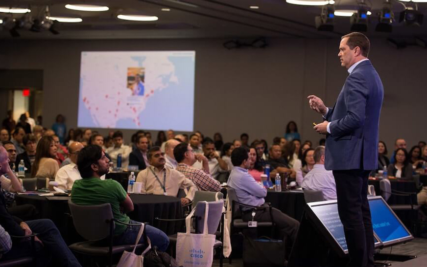 Cisco manager holding a talk at the CiscoLeaderDay meeting while social media post pop up on a social media map projected on the wall.