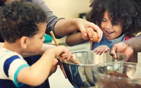 hashtag campaign for encouraging kids to eat healthy. this picture shows two kids cooking together with 2 adults.
