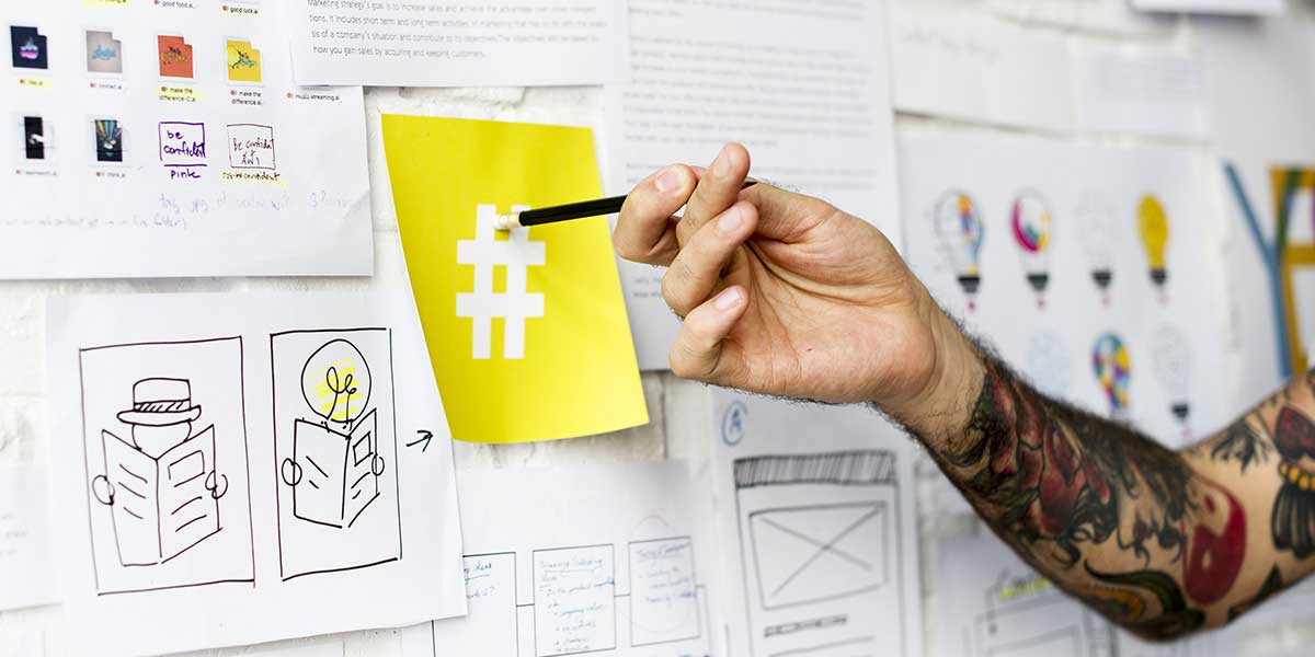 hashtag campaign social wall page featured image showing a man's tattooed hand pointing to a hashtag sign post it on a wall