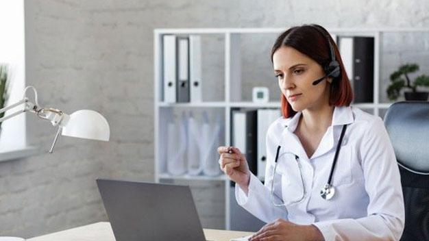 Healthcare provider showing man assessment on laptop