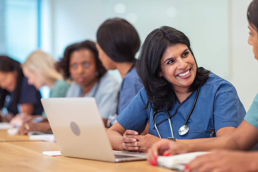A middle aged female nurse smiling and sitting in front of a laptop