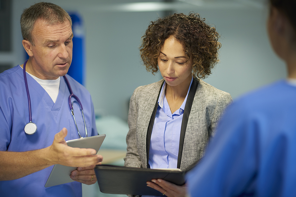 A hospital administrator holding an iPad as she speaks with a male nurse