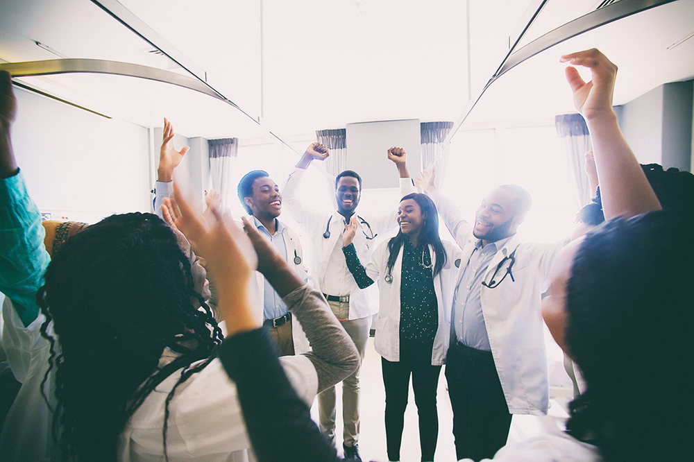 A group of hospital administrators cheering with arms in the air
