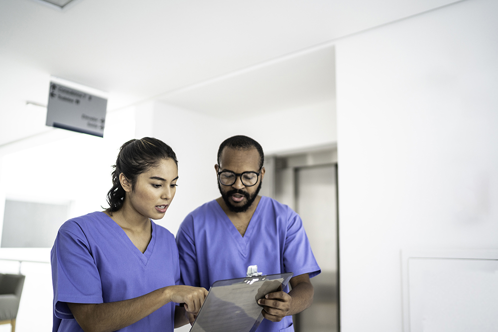 A female and male nurse huddled closely together in front of an elevator as they review a clipboard with a patient's chart