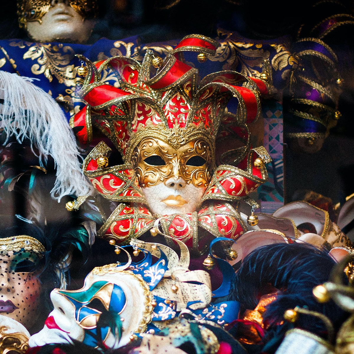 A mardi gras mask sitting atop a pile of mardi gras paraphernalia.