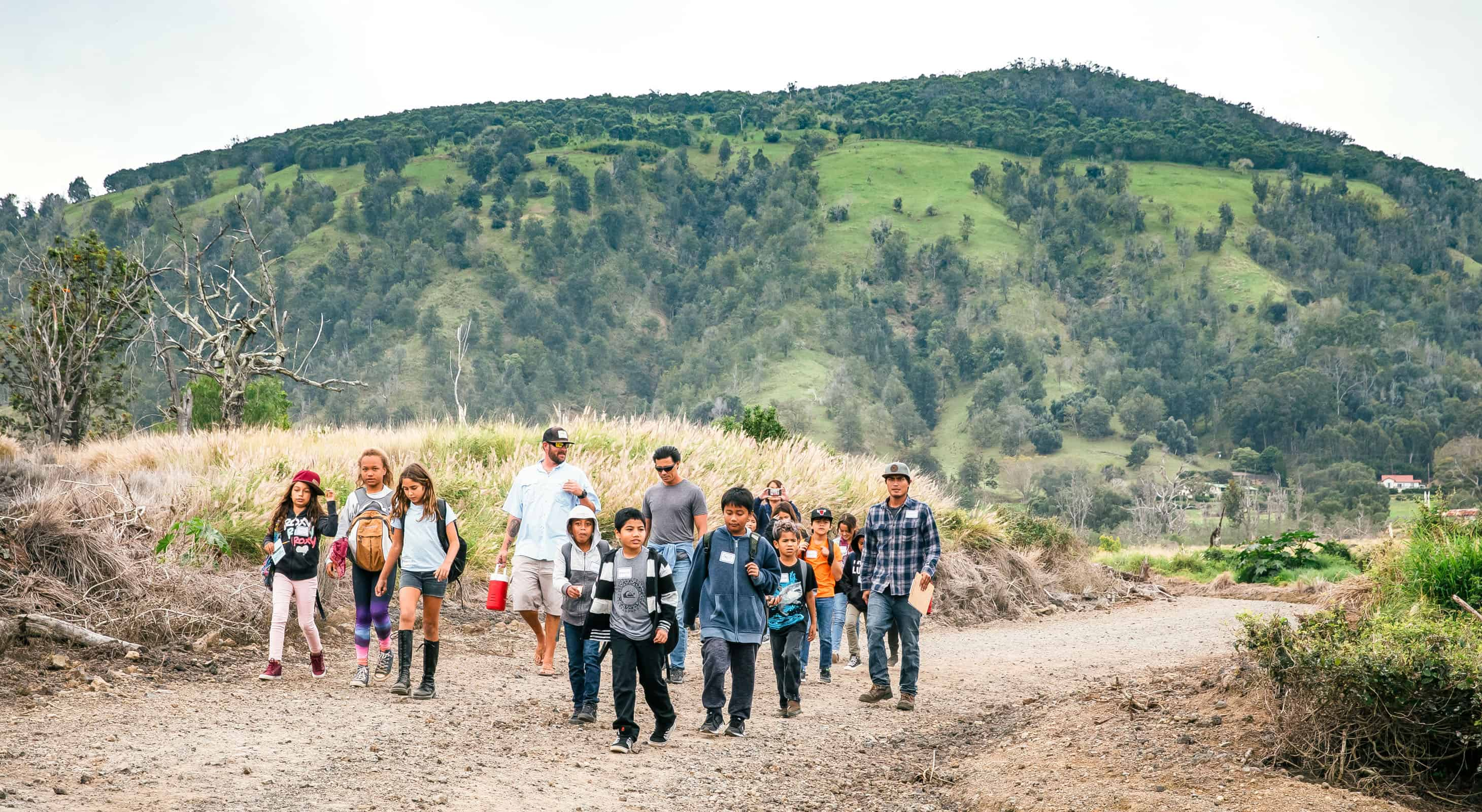 A group of young students walking on a road near Puʻu Waʻawaʻa