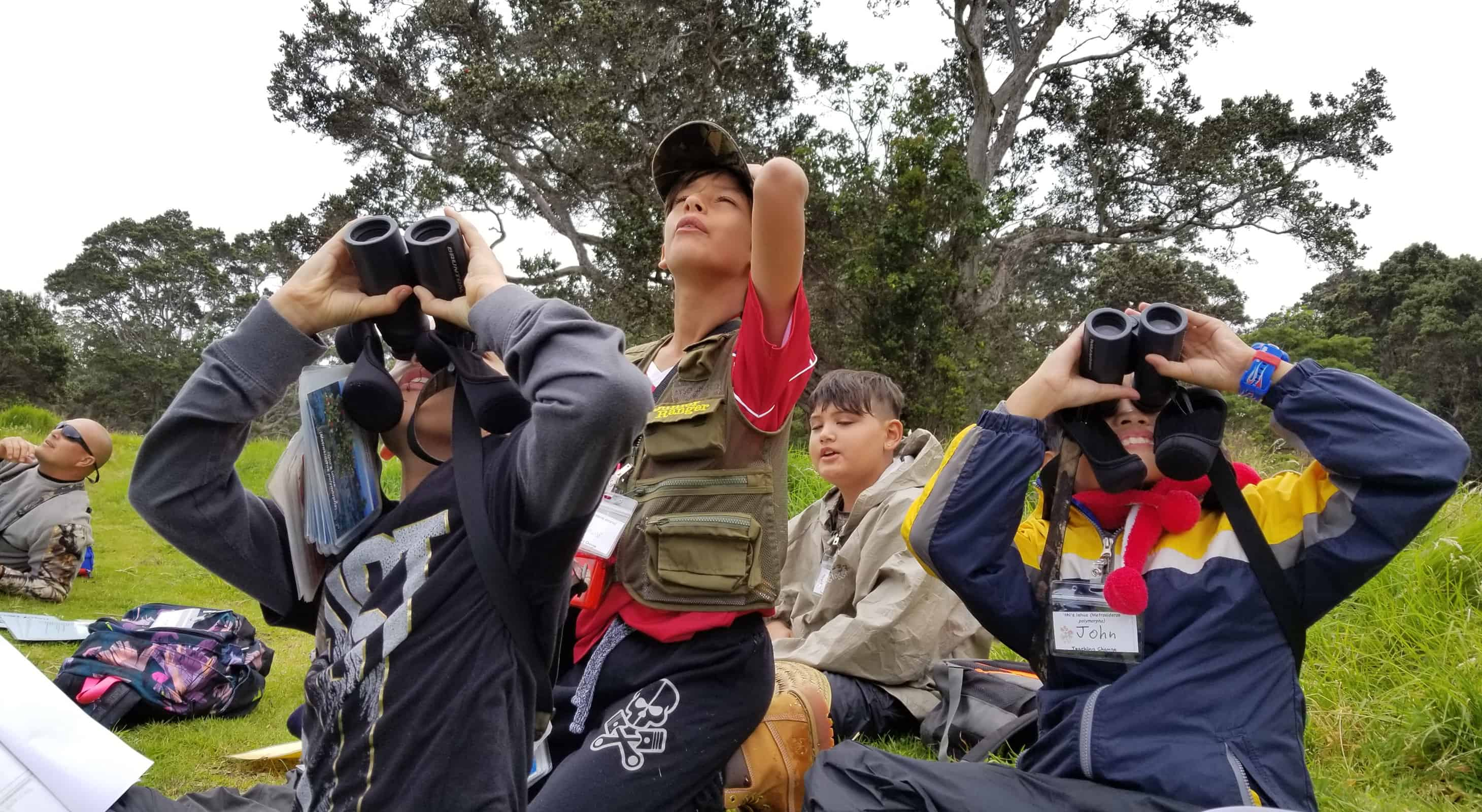 Students gather and look at birds through binoculars