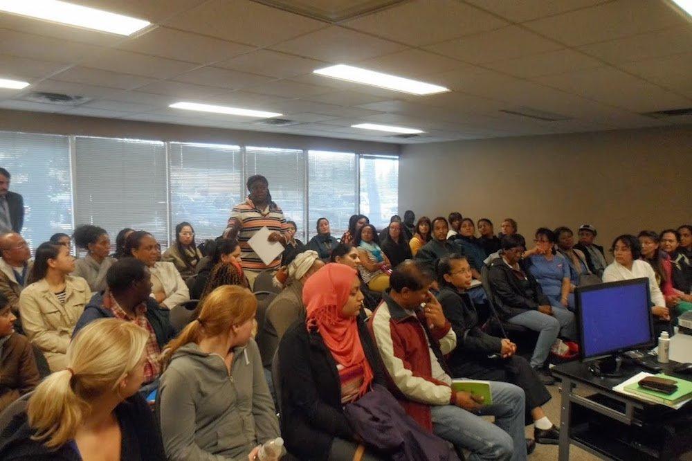 Woman standing up asking questions at a job seminar.