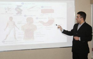 Teacher at projection screen instructing human anatomy class.