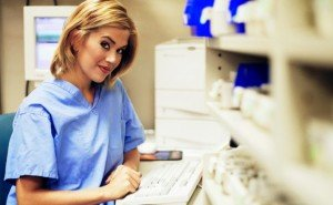 Girl in blue nursing shirt at computer desk.