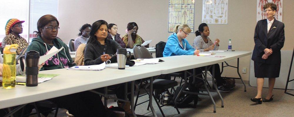 Students at their tables watching the job seminar presentation.