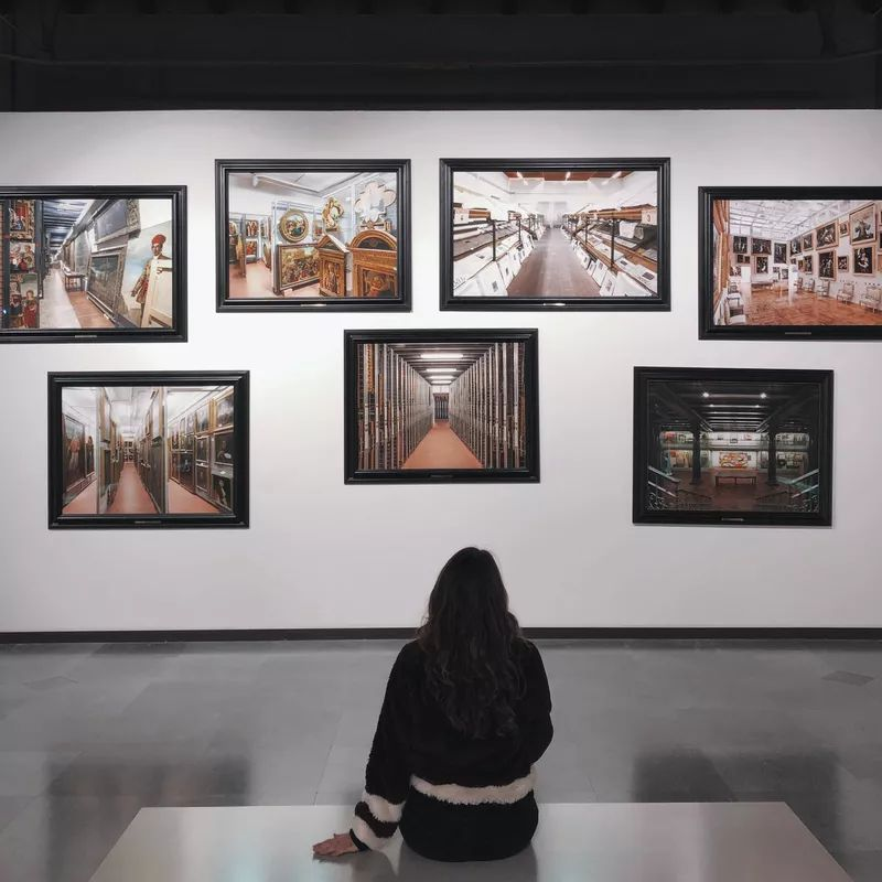 Woman sitting in from of a wall of pictures