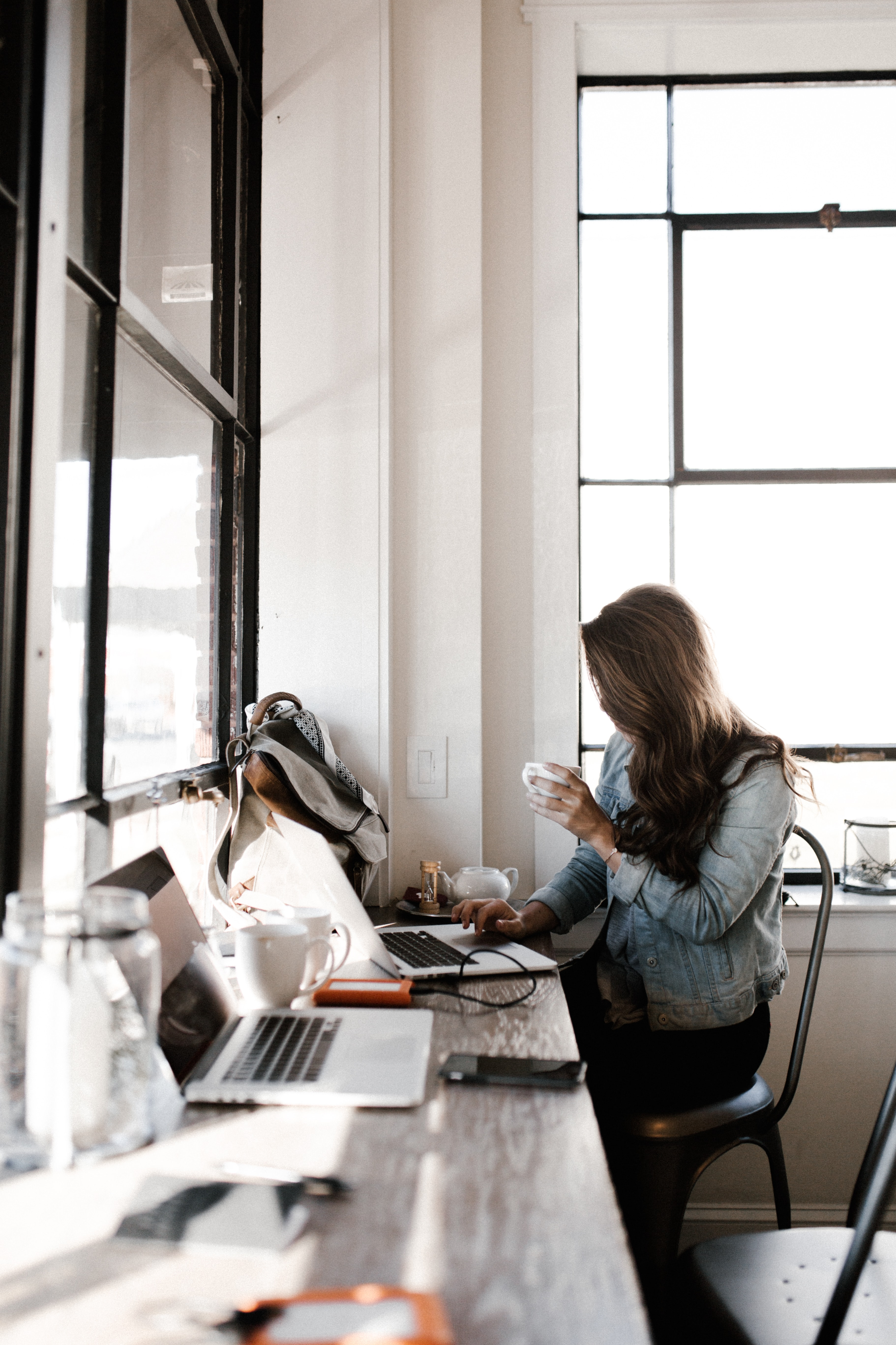 woman works at desk on laptop using technology