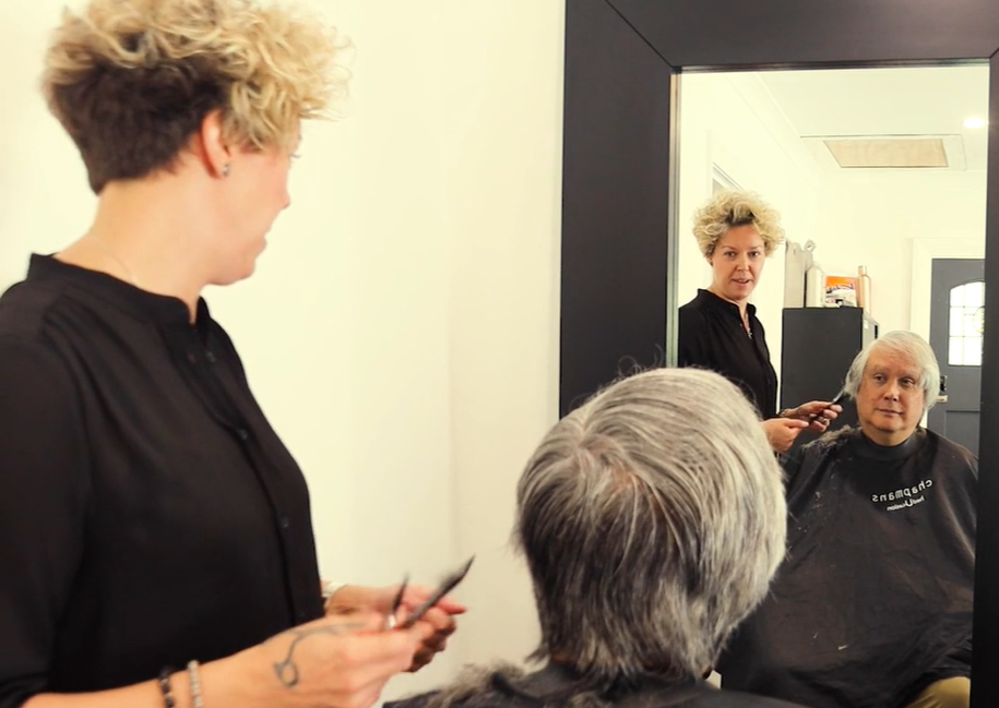 An image of a woman cutting a man's hair and talking to each other