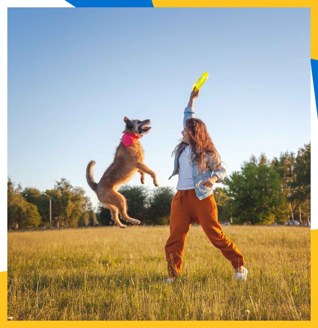 Woman holding frisbee in the air  while her dog leaps for it.