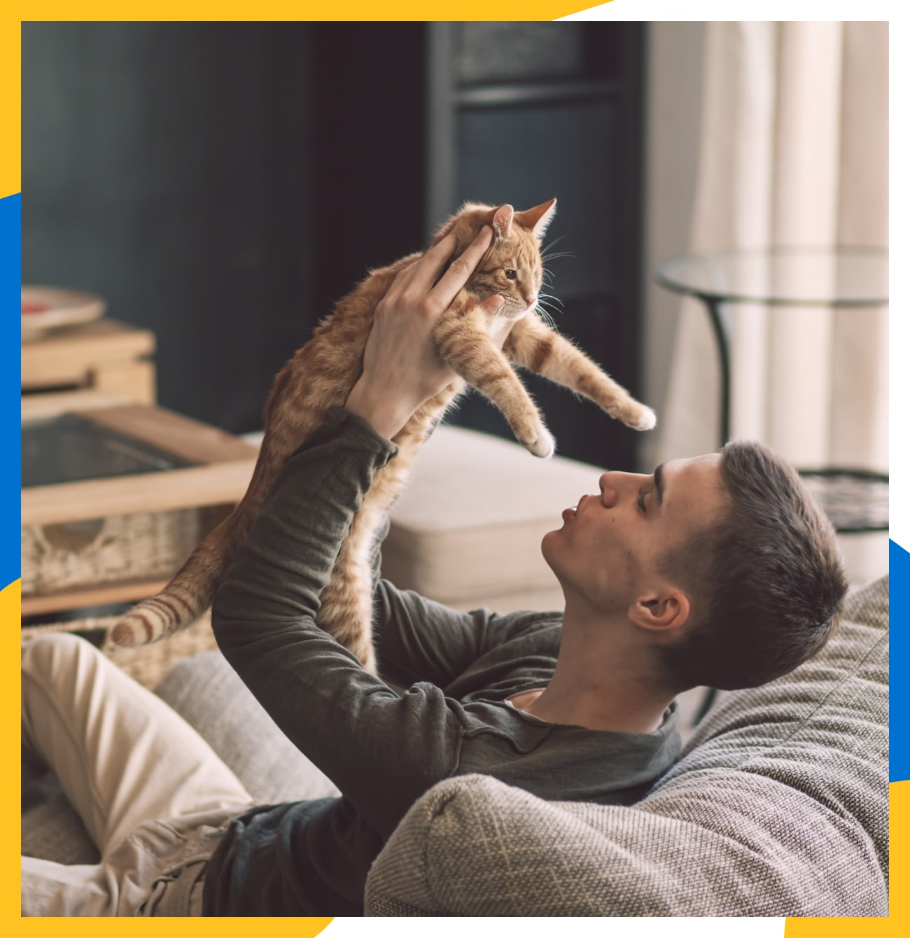 A young man, holding his cat up in the air and making a kiss face