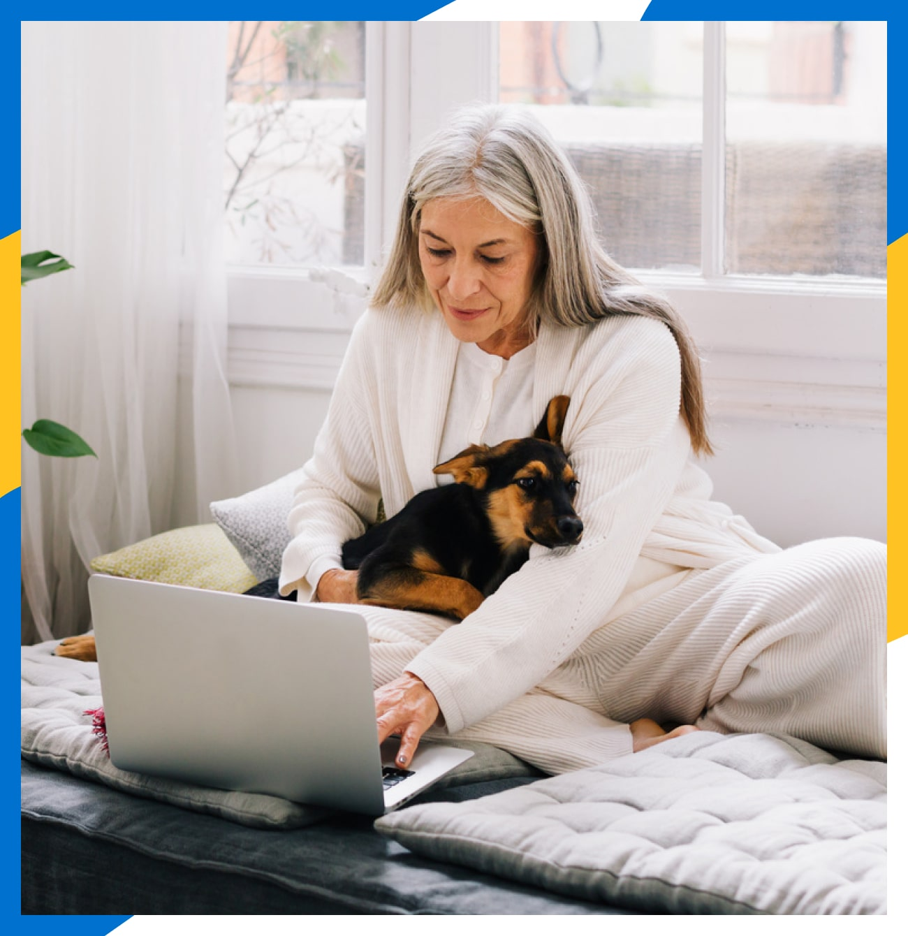 Older woman holds her German Shepherd puppy while working on her laptop