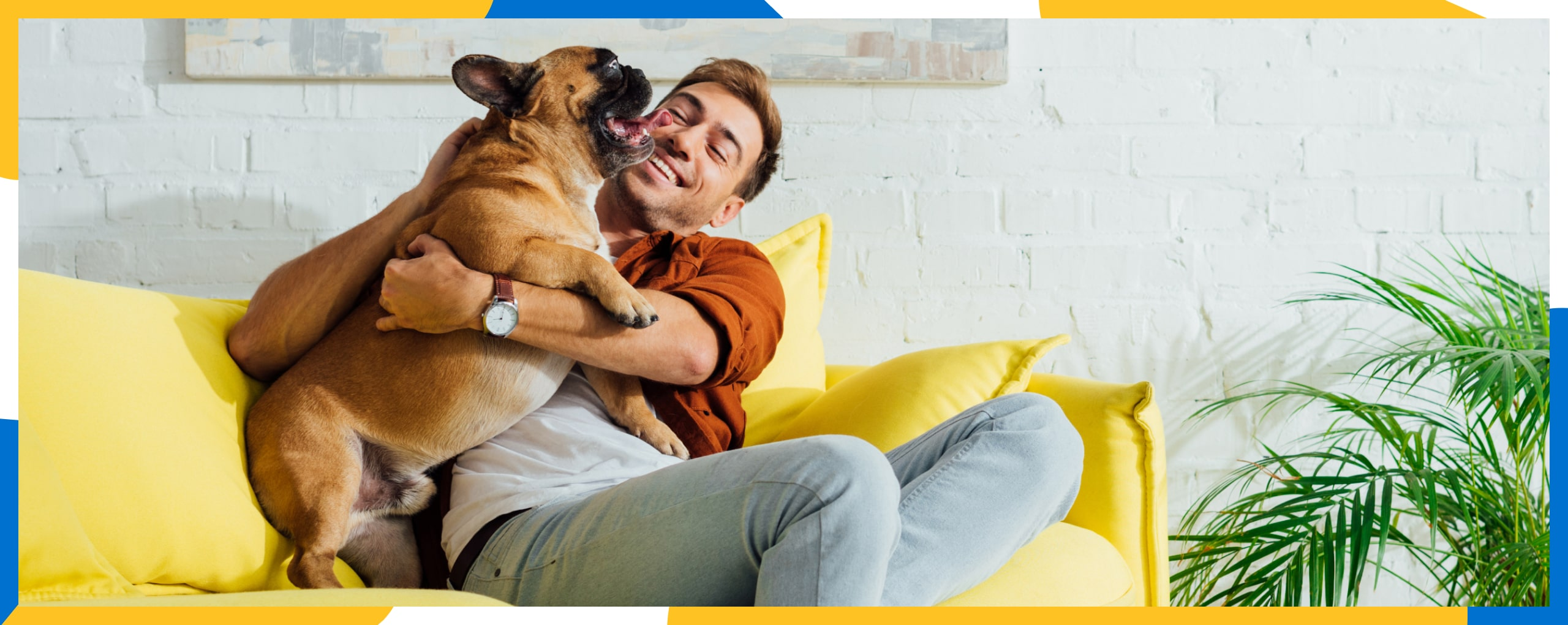 A young man hugging his happy pug and smiling wide