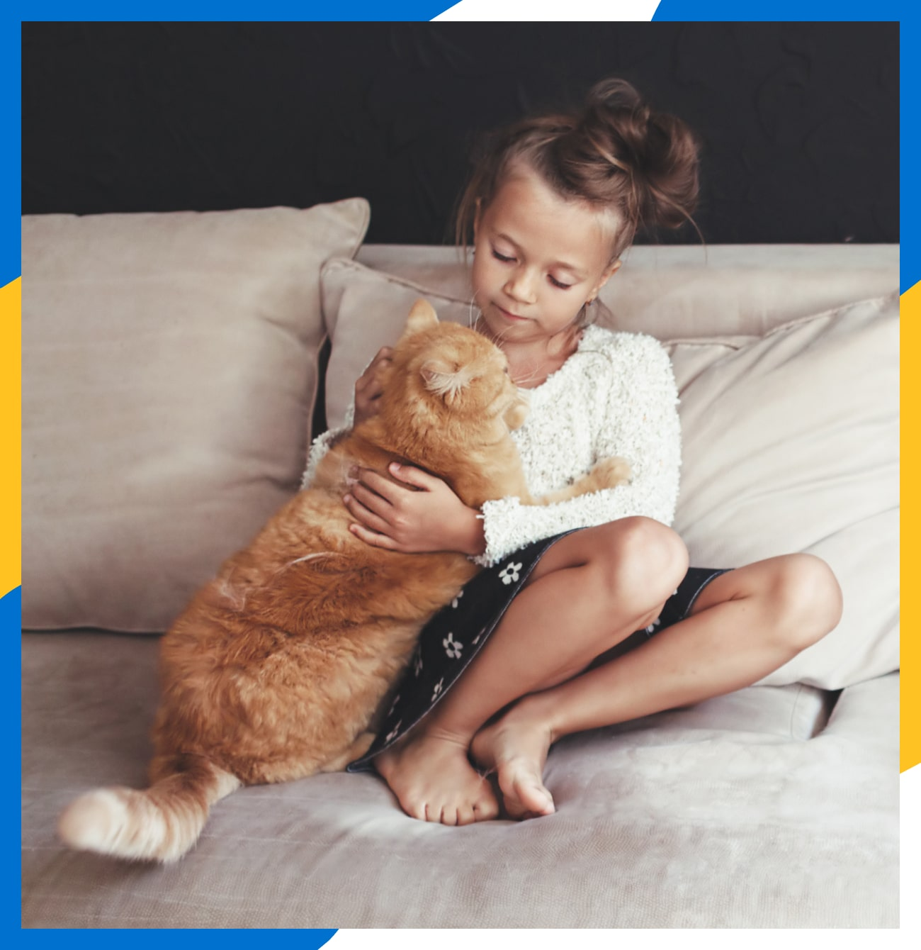 A little girl sitting on the couch holding a large cat.