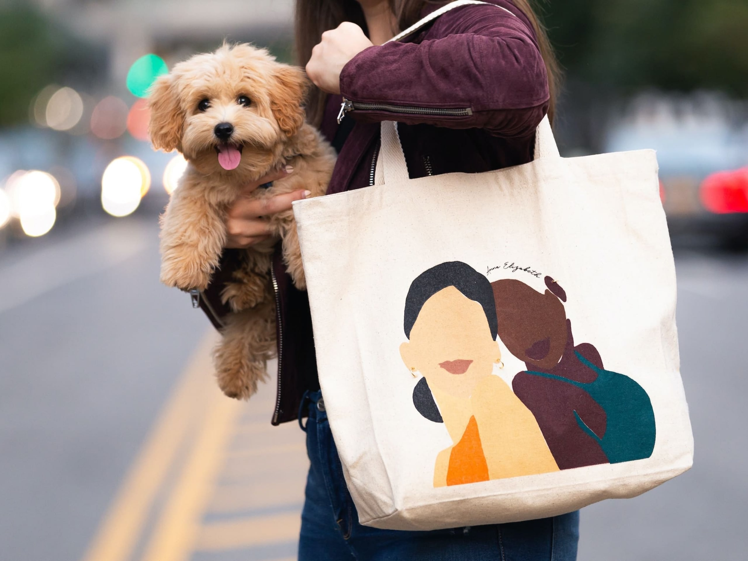 A person walking across the street with a young puppy in one hand, and a reusable bag in the other.