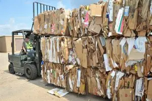 Forklift adding a bale of cardboard to a stack of cardboard bales