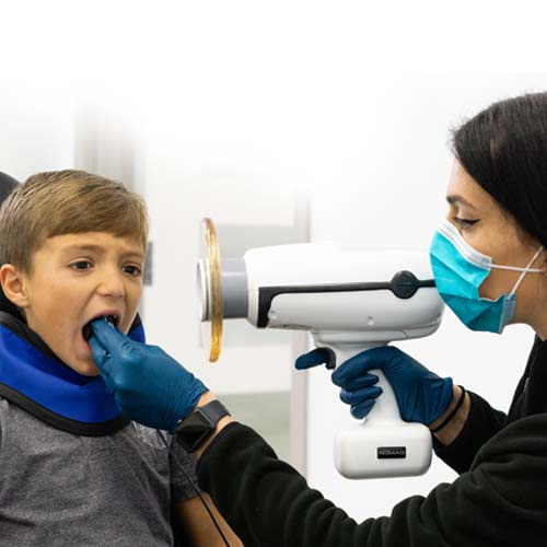 Staff member taking an x-ray of patient's mouth