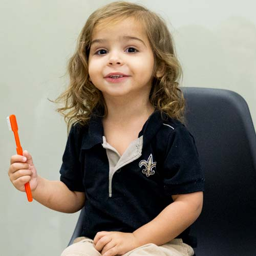 Child patient smiling with toothbrush in hand