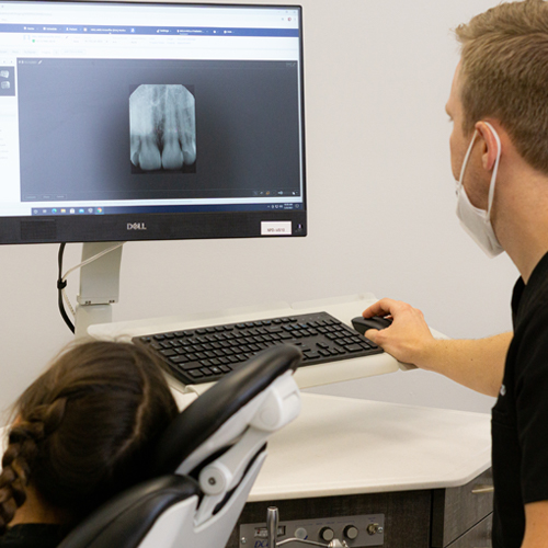 Kristoffer Norbo DDS, MSD looking at x-rays with patient