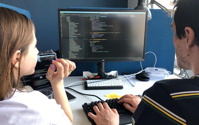 Zwei Mitarbeiter schauen auf einen Computerbildschirm