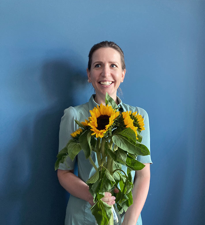 Mitarbeiterin hält Sonnenblumen in der Hand vor einem blauen Hintergrund