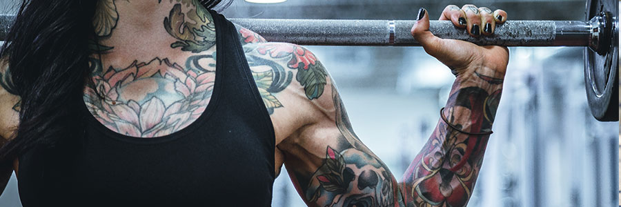 Women with tattoos lifting weights