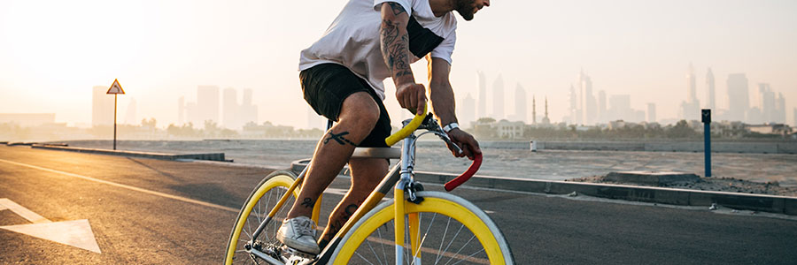 Man on bicycle on road with city in background