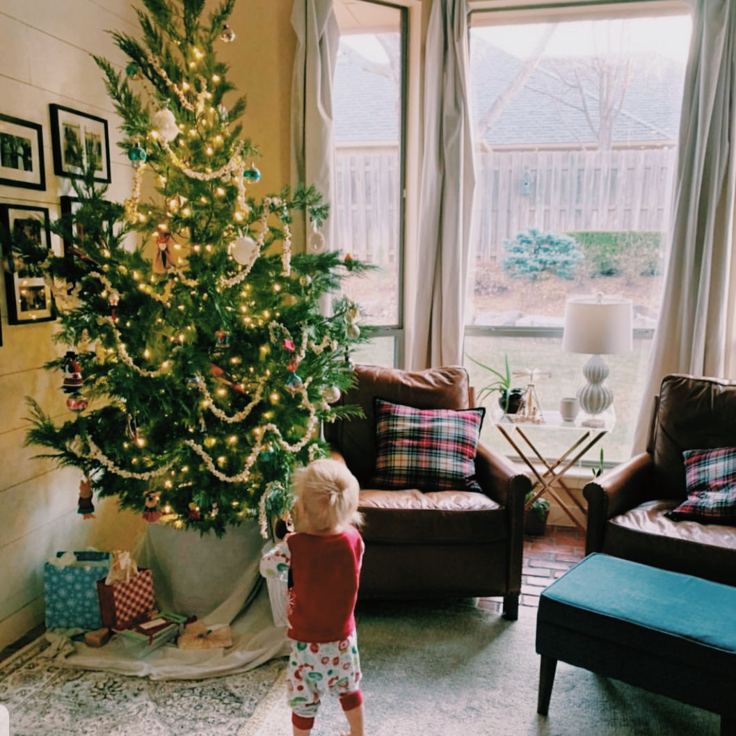 a baby approaches a brightly lit and decorated christmas tree