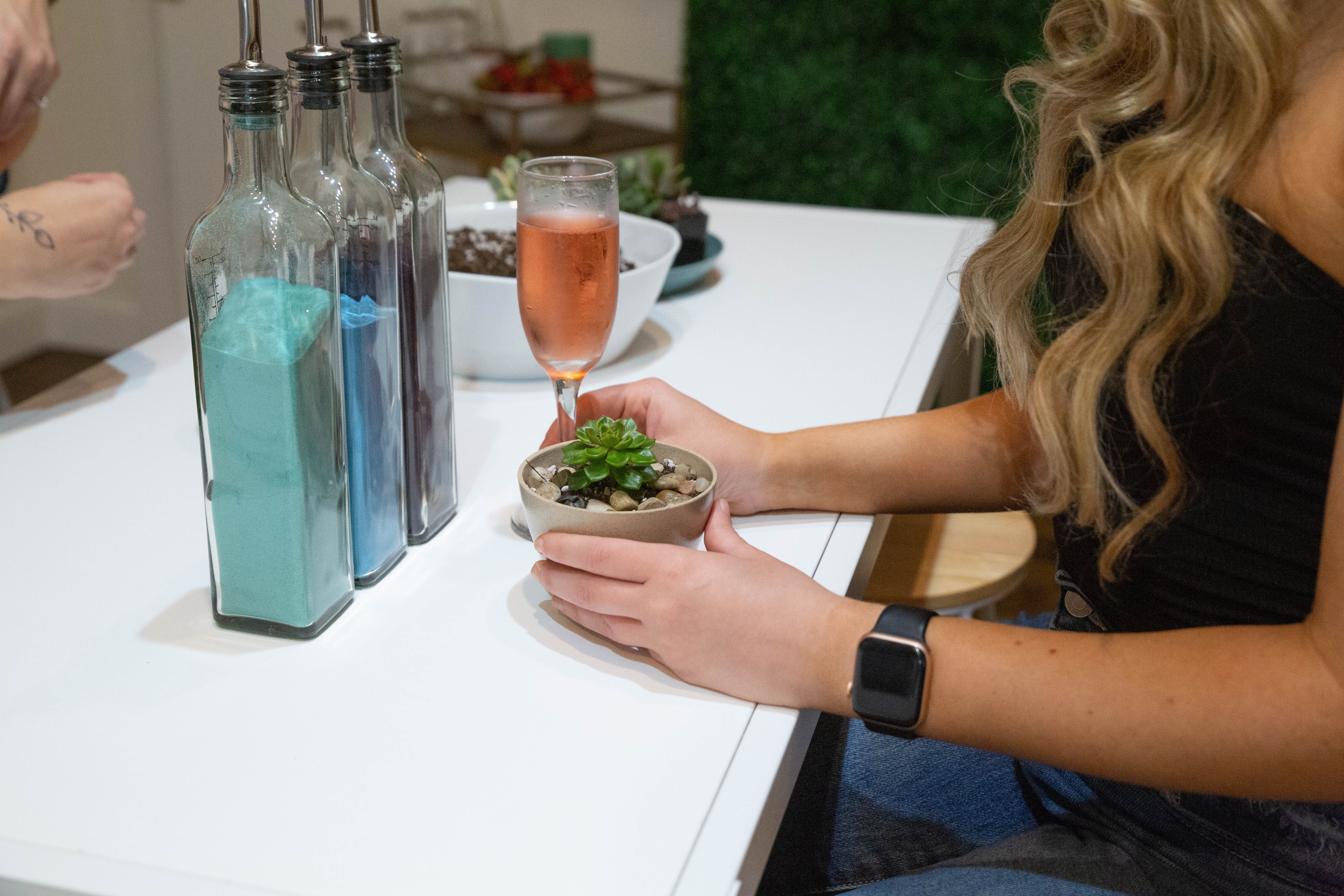 A young woman is sitting at a white table. In front of her is a small succulent in a planter and a glass of sparkling rose as well as supplies to plant more succulents, including jars of brightly colored decorative sand.