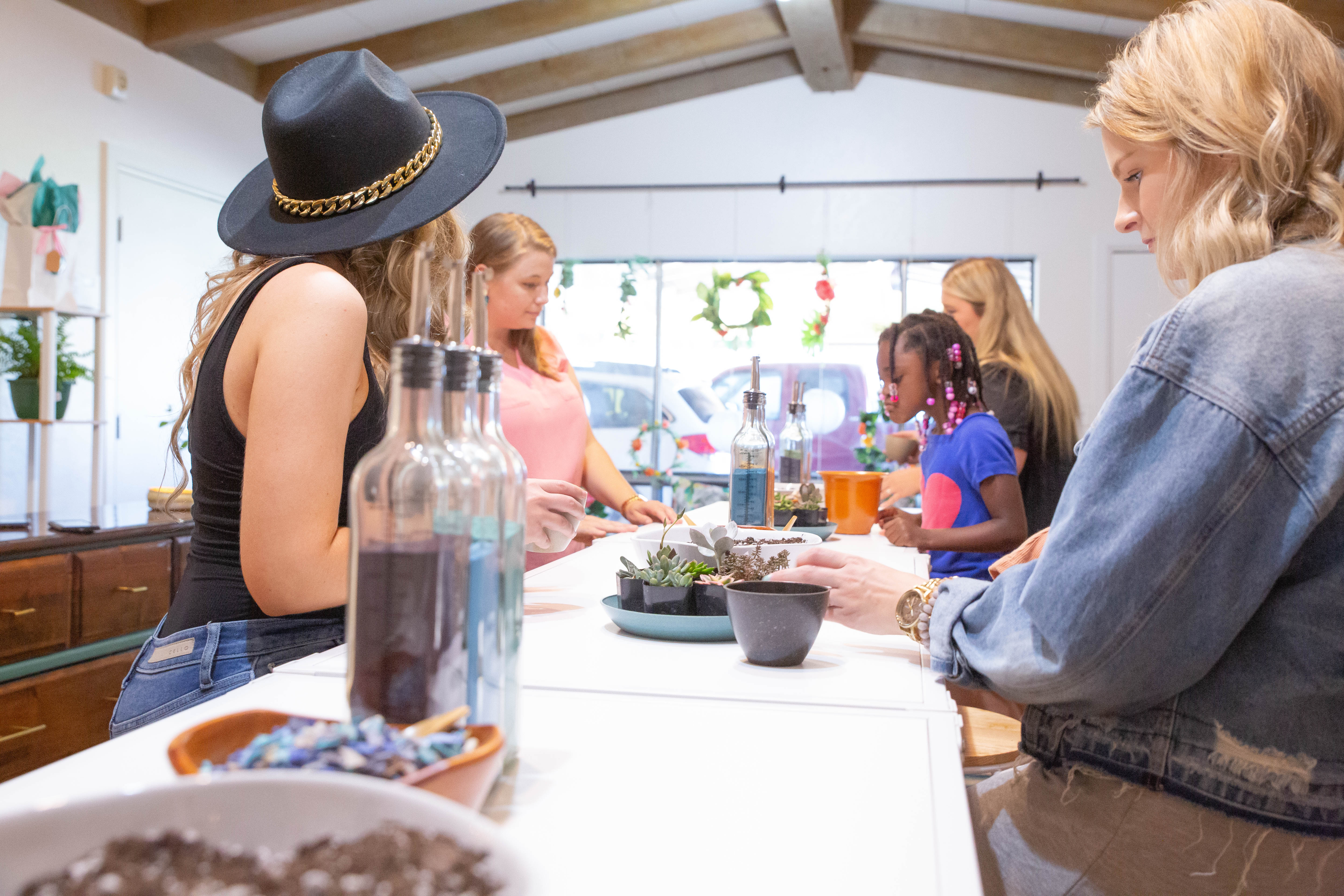 Young women and a child plant succulents into planters at table in a colorful, brightly lit room.