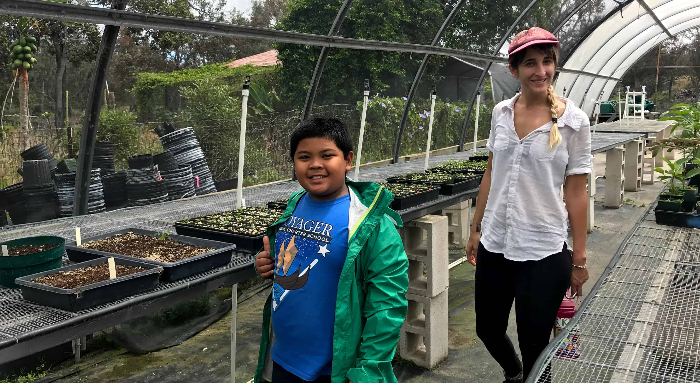 Teaching Change staff working with a student in a greenhouse