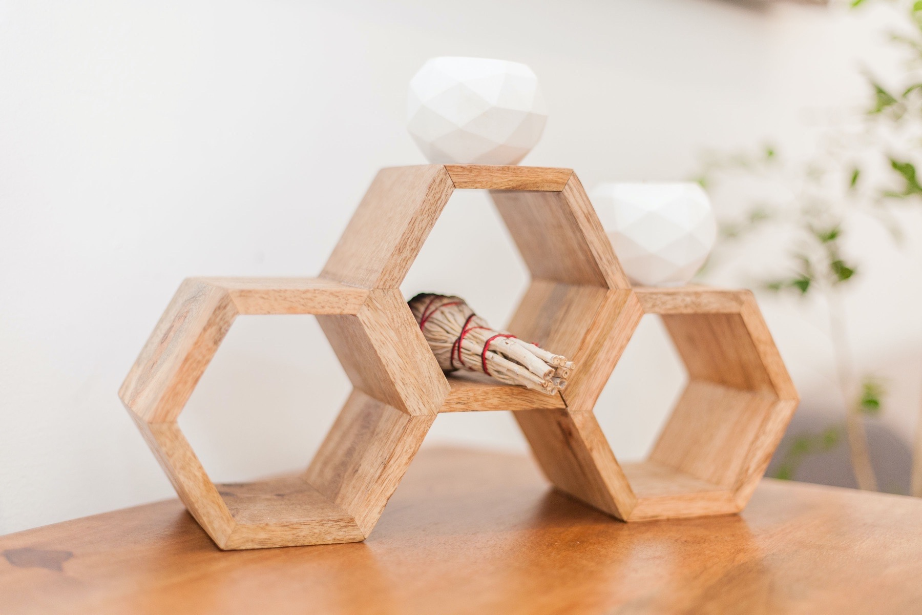 Three part hexagonal structure with candle and burning sage.